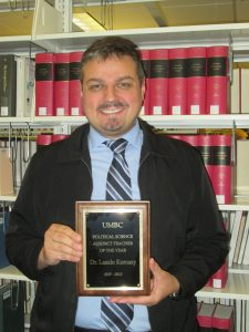 Picture of Laszlo Korossy holding his UMBC plaque award as UMBC's Political Science Adjunct Teacher of the Year dated in 2017-2018. He stands in front of a shelve of red books located in a library.
