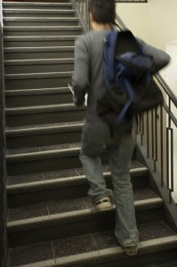 Photo of a student walking upstairs with an unzipped blue backpack slung over his right arm.