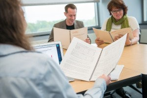 Three people reading through UMBC spiral bound packets, performing a group evaluation.