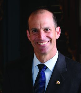 Headshot of Jon Cardin wearing a black suit and blue tie formally patterned with multiple white dots in a grid-like fashion.